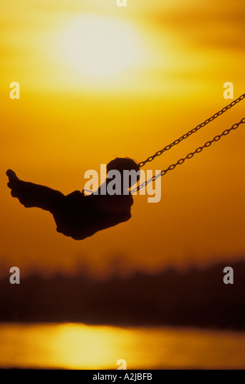 Silhouetted by the setting sun a young child soars high on a swing - Stock Image
