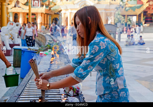 Burmese girl burning incense sticks / joss sticks in the Shwedagon Zedi Daw Pagoda at Yangon / Rangoon, Myanmar - Stock Image