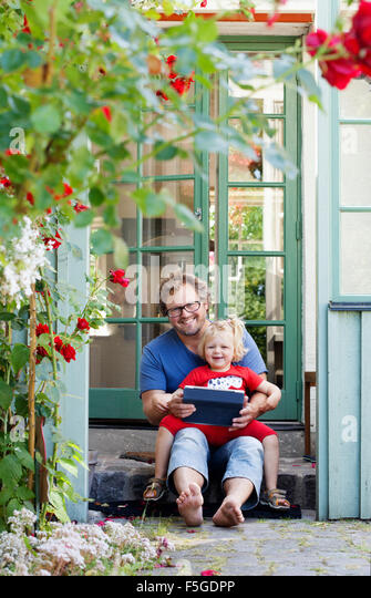 Sweden, Skane, Mossby, Portrait of daughter with father holding tablet pc - Stock Image