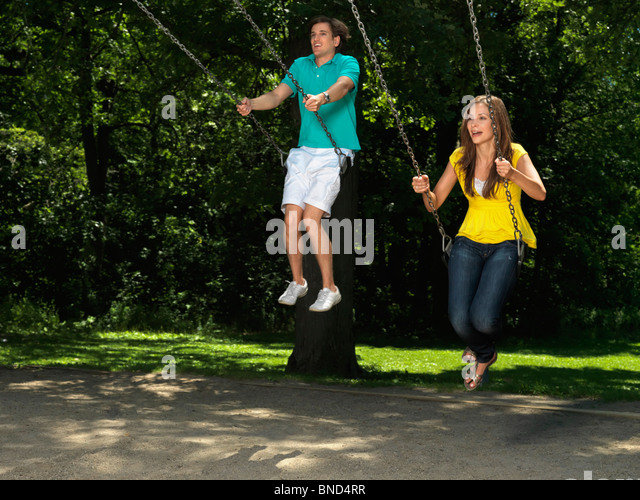 Young couple in their thirties having fun on a swing at children's playground - Stock Image