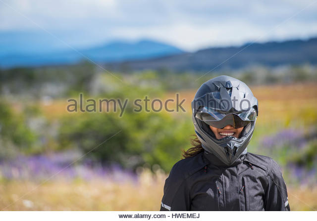 Woman in motorbike clothes and helmet laughing at camera, Puerto Natales, Patagonia, Chile - Stock-Bilder
