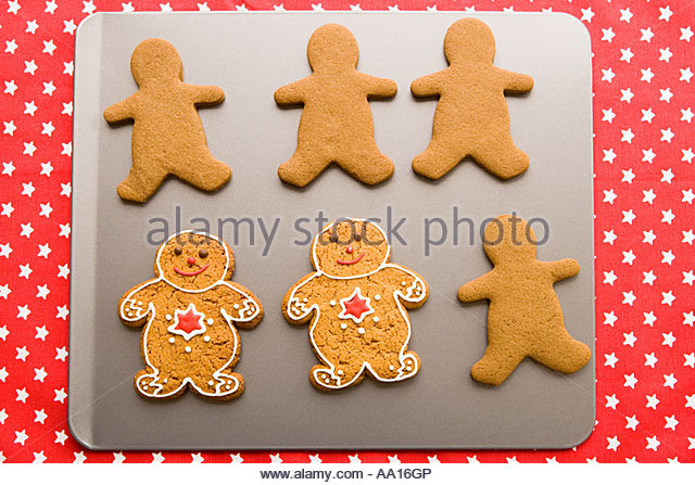 Gingerbread men on a baking tray - Stock Image