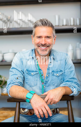 Smiling Caucasian man leaning on chair in store - Stock-Bilder