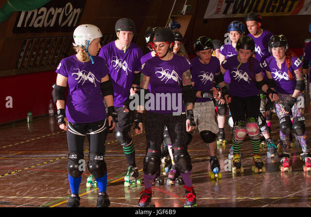 Roller derby skaters in purple warming up - Stock Image