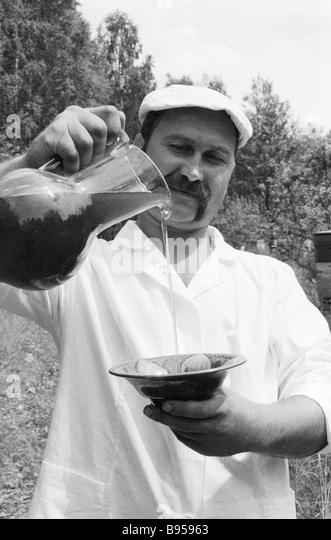 Beekeeper shows buckwheat honey - Stock Image
