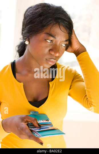 young woman putting credit card in purse - Stock Image