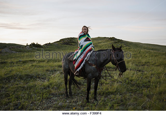 Portrait female rancher on horseback wrapped in blanket - Stock-Bilder