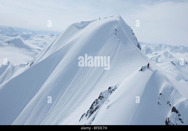 Two skiers on a snowy mountain getting ready to drop in Haines, Alaska. - Stock Image