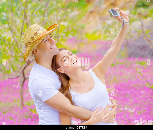 Cute cheerful couple make photo of themself outdoors on beautiful pink floral meadow in summer garden, affection - Stock-Bilder