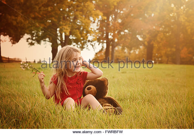 A little girl is sitting outside in the country with green grass and sunshine for a happiness or nature concept. - Stock Image