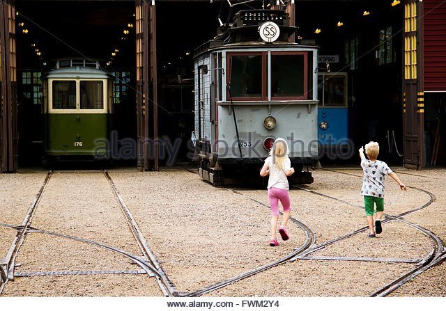 Full Length Rear View Of Girl And Boy Running Towards Train At Museum - Stock Image
