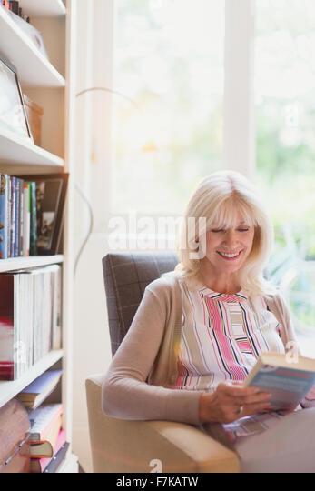 Smiling senior woman reading book in den - Stock Image