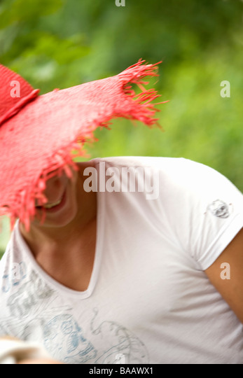 A man wearing a red sun hat, Sweden. - Stock Image
