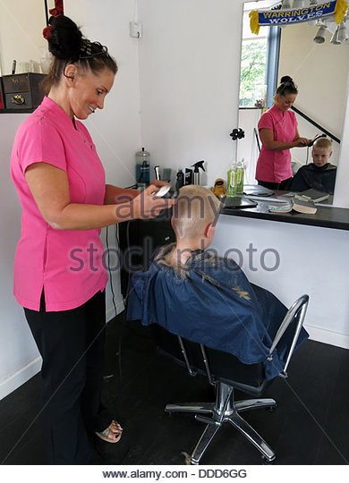 Small boy having a haircut with blond hair - Stock Image