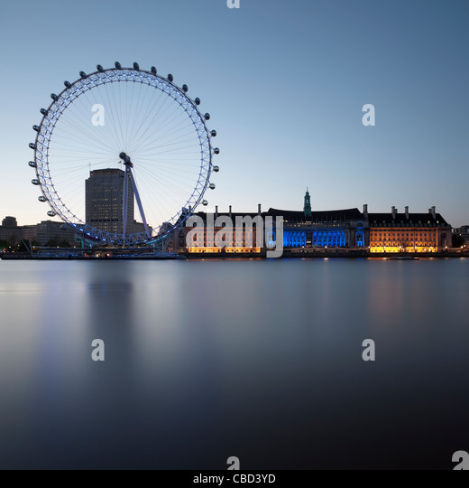 London Eye and building by still river - Stock Image