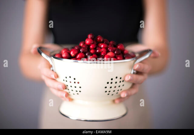 Bright red cranberries in a cream colored strainer being held by a woman. - Stock Image