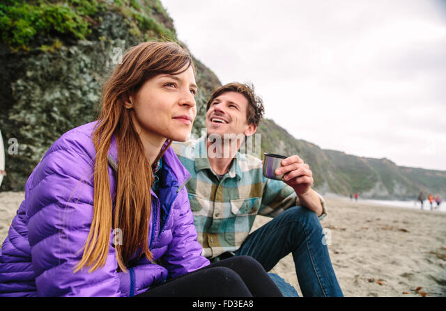 A young couple enjoying an afternoon on the beaches of Big Sur, California. - Stock Image