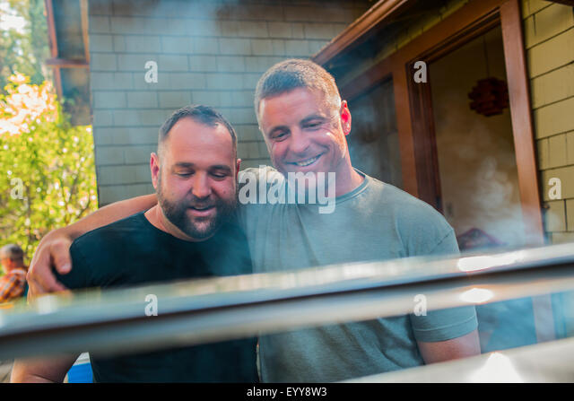 Gay couple grilling food in backyard - Stock Image