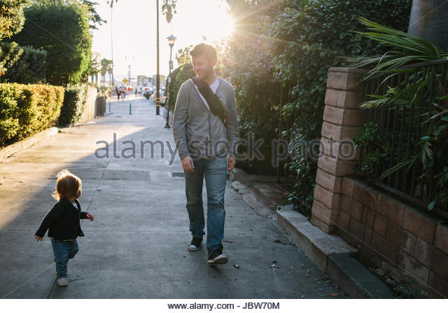 Father and baby boy walking in residential street, Venice Beach, Los Angeles, California, USA - Stock-Bilder