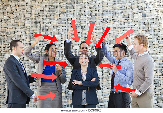 Group of business people pointing arrows towards businesswoman - Stock Image