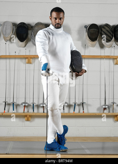 Portrait of a fencer wearing fencing uniform in a gym - Stock Image