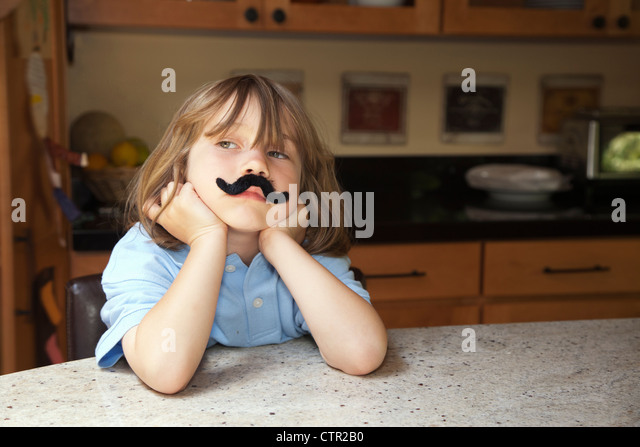 Little girl in the kitchen wearing a fake mustache. - Stock Image