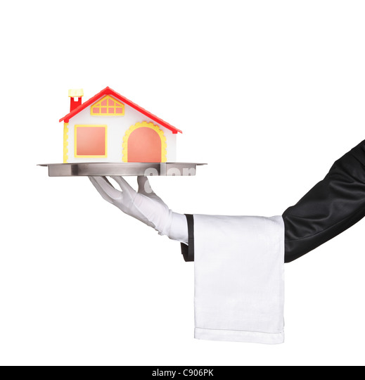 A waiter holding a silver tray with a house model on it - Stock Image