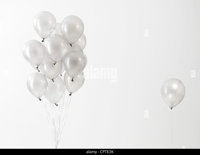 Silver balloons floating against white background - Stock Image