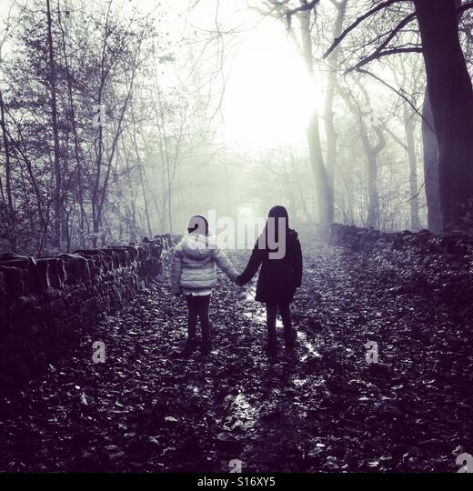 Two children holding hands in the woods. - Stock-Bilder