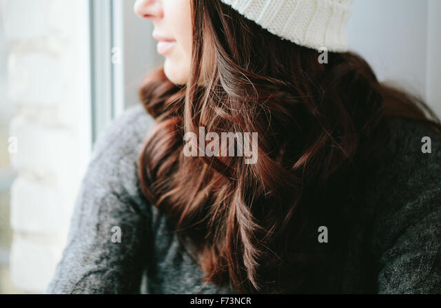 Girl in a cap looks out of the window. - Stock-Bilder