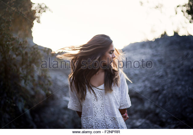 Mixed race woman turning in remote field - Stock-Bilder
