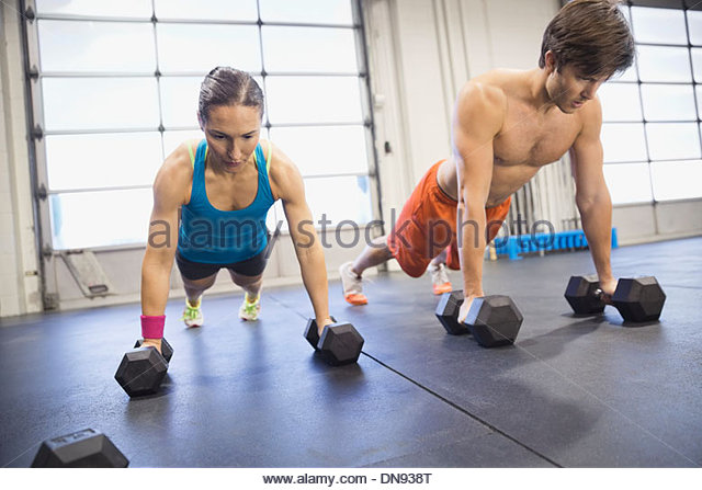 Athletes practicing dumbbell pushup rows - Stock Image