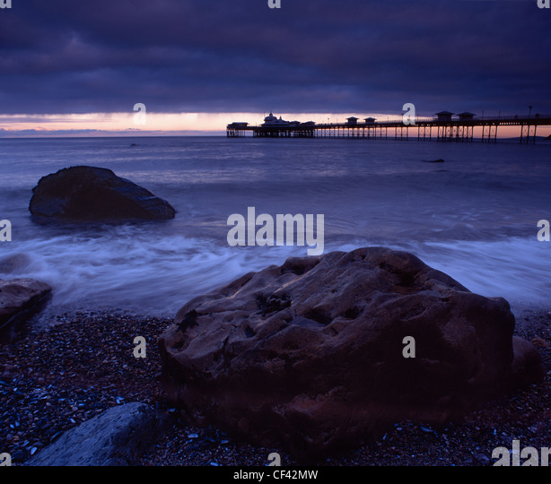 View over large boulders on the seashore towards Llandudno Pier at dusk. - Stock-Bilder