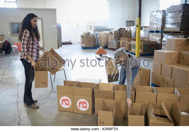 Female volunteers preparing donation boxes in warehouse - Stock Image