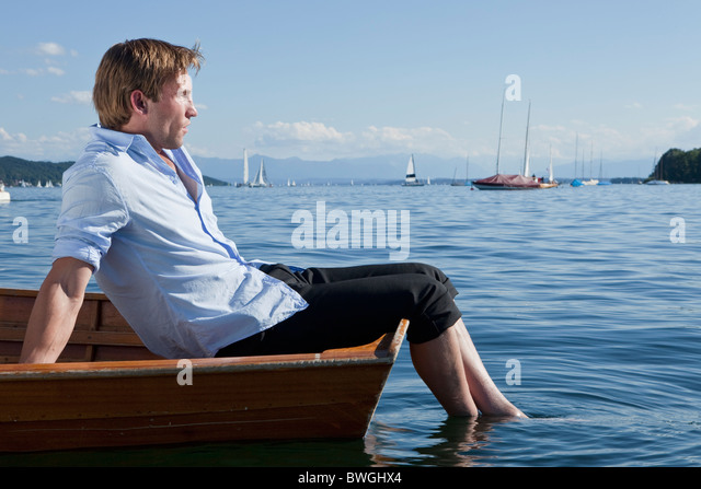 Businessman relaxing on a rowboat - Stock Image