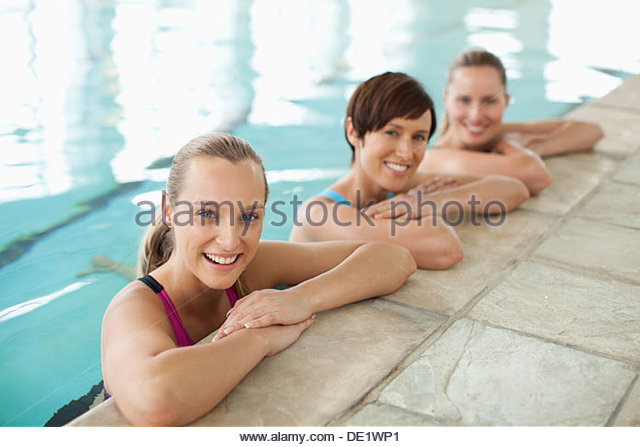 Portrait of smiling women leaning on edge of swimming pool - Stock Image