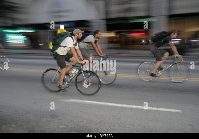 Georgia Atlanta Peachtree Street downtown street man group young adult bicycle cyclist cap ride motion - Stock Image