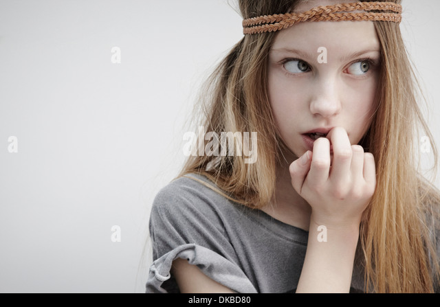 Portrait of girl wearing leather braid around head, holding feather, finger in mouth - Stock-Bilder
