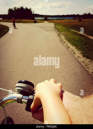 Cropped Image of Man Assisting Boy In Riding Bicycle On Road - Stock Image