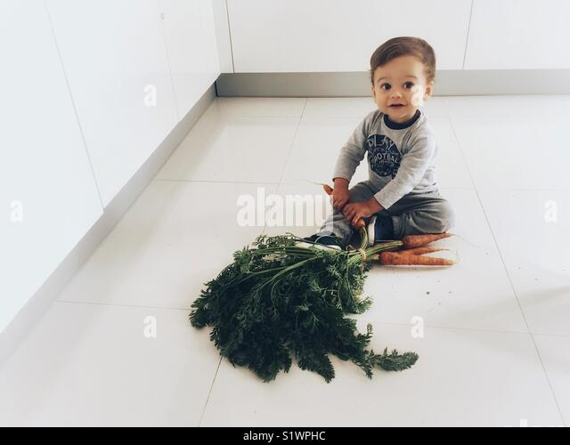 A toddler discovers carrots. - Stock Image