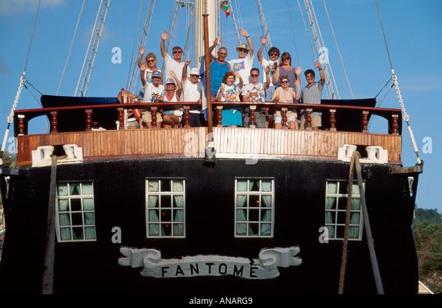 Grenada St. George's Carenage Harbor Barefoot Windjammer SV Fantome schooner cruise ship passengers wave - Stock Image