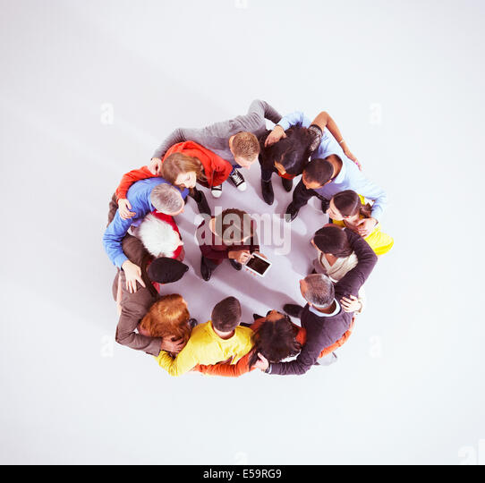 Business people huddled around woman with digital tablet - Stock-Bilder
