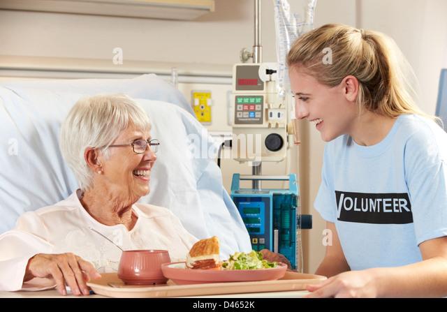 Teenage Volunteer Serving Senior Female Patient Meal In Hospital Bed - Stock Image