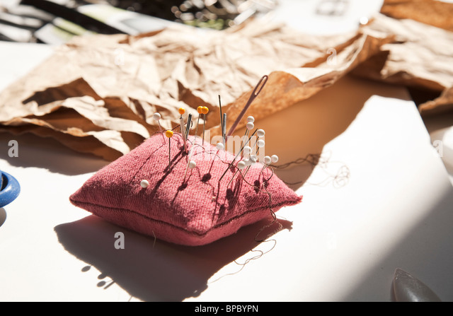Pincushion with needles / pins on a cutting mat - Stock Image