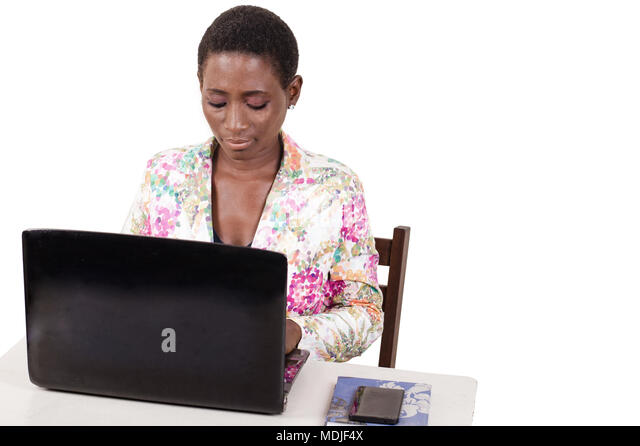 Young woman sitting in office working on laptop - Stock Image