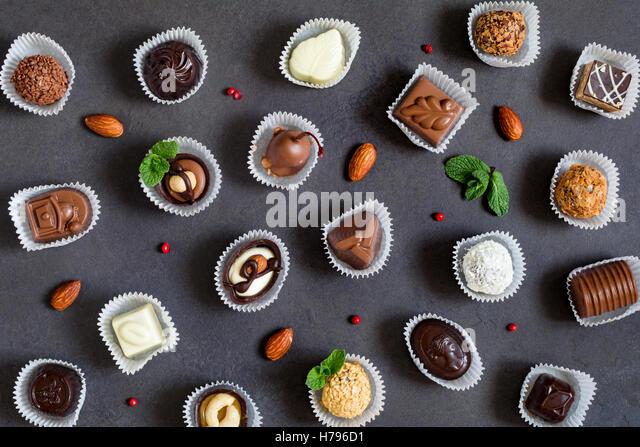 Fine chocolates pattern on dark background - Stock Image