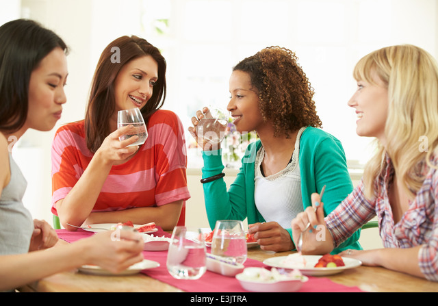Group Of Women Sitting Around Table Eating Dessert - Stock Image