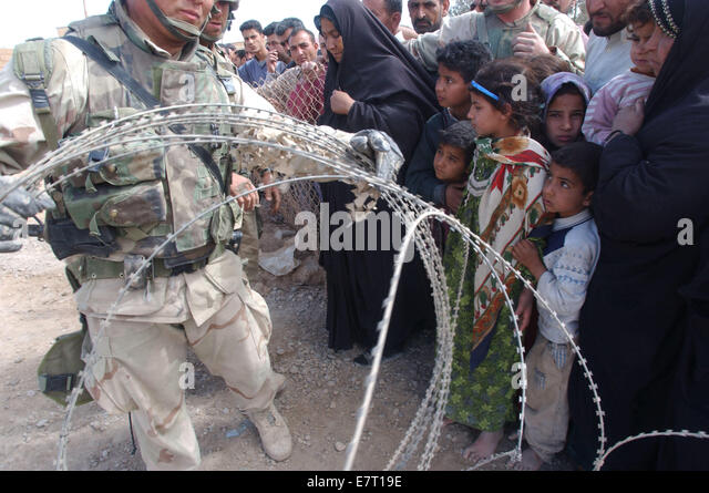 (PUBLISHED 04/11/2003, A-5; 04/11/2003 SIGNON SAN DIEGO): Iraqi children watch Marines from the lst LAR string barbed - Stock-Bilder