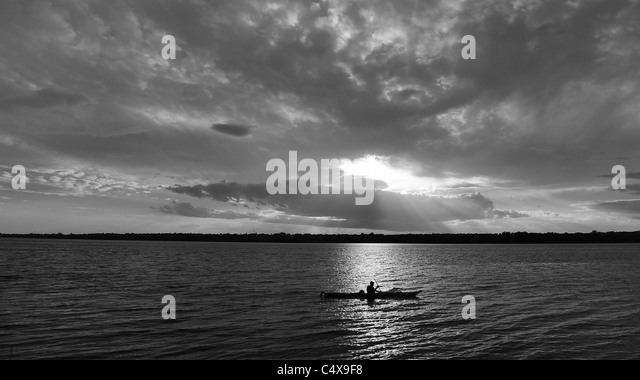 Lone kayak silhouetted on scenic lake at sunset. - Stock Image