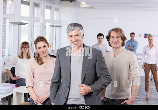 Germany, Bavaria, Munich, Mature man with colleagues standing in office, smiling - Stock Image